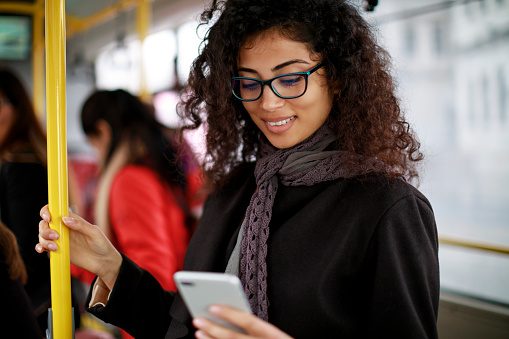 Smiling young woman traveling by bus and using smart phone